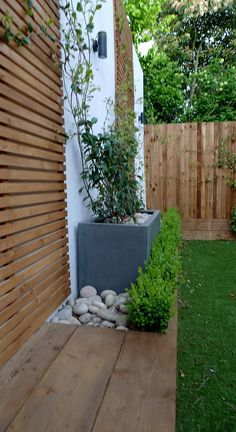 Pine slatted softwood horizontal screen, deck edged grass and pebbles.