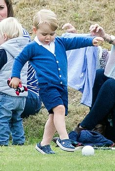 Prince George kicks a polo ball as his family watch Prince William playing polo with Prince Harry
