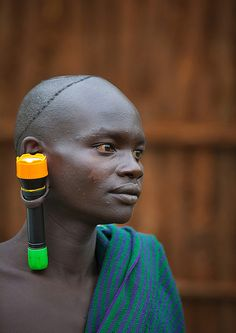 Suri Tribe Man With An Enlarged Ear Decorated With A torch, Kibish, Omo Valley, Ethiopia   by Eric Lafforgue