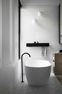 Freestanding modern tub with black faucet and towel bar