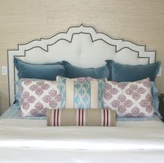 upholstered headboard shape, contrast cording on headboard, mix of pillows, mixed bedding