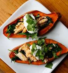 We took what is usually a greasy bar snack and turned it into a delicious appetizer that is healthy enough to eat for a meal! These baked sweet potato skins are topped with spinach, spiced chicken, and cilantro, with a dollop of Greek yogurt. // dinners // lunches // snacks // healthy recipes // bar food // Beachbody // BeachbodyBlog.com