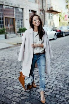 Gray coat over white knit sweater and blue jeans.