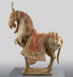 China, Six Dynasties (549 - 577)    Chinese Caparisoned Horse Statuette  A Ceramic model horse in full military comparison with decorated saddle blanket, bridle, crupper and collar with modelled D-shaped pendants and erect forelock.