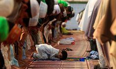 RAWALPINDI: A boy attends Eidul Fitr prayers with others at Jamia Masjid on Wednesday. —REUTERS/Faisal Mahmood