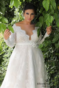 Irresistable in a plus size French lace wedding gown with long sleeves and a deep V-neck. Sophia. Studio Levana