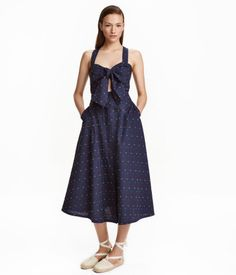 Calf-length, gently flared dress in cotton plumeti fabric. Sundress-style bodice with wide, adjustable shoulder straps that can be crossed at back. Wide ties at front and concealed hook-and-eye fasteners at neckline. Sun bodice can be detached from skirt with concealed buttons. Skirt with elastication at back of waistband, concealed buttons at front, and side pockets. Unlined.