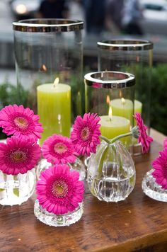 Atop a wooden table, green pillar candles compliment pink gerbera daisies for a spring outdoor wedding.