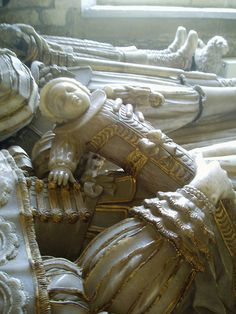 Infant @ Elmley Castle's church the Savage family in the north transept.  It commemorates two generations, William Savage (d.16160, his son Giles Savage (d.1631) & his wife Catherine (d.1674) who holds a baby, a poignant reminder of how common child mortality once was.   The monument is the work of Samuel Baldwin of Stroud and is of excellent quality, beautifully carved with exquisite details, with gold leaf used to pick out various details of the costumes.