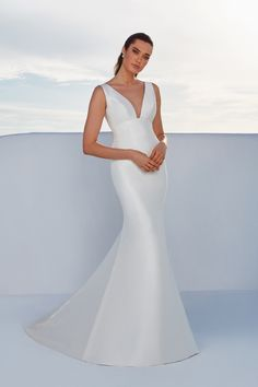 Show off your shape in this sleek fit and flare Mikado gown. It will have you feeling confident and sexy with the plunging neckline in the front and back with matching buttons from the neckline to the hem. Paired with a full detachable chapel length train that completes the look. A raised neckline version is also available with this style.