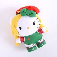 Woah! Hello Kitty looks hecka fierce today - who knew she loved *Street Fighter* so much! Here she is in another cool *Street Fighter* cosplay, this time as her fellow countrywoman, British special forces officer Cammy. Dressed in Cammy's regular military Delta Red uniform, Hello Kitty is here to take care of business! Take her home today in the form of this cute mini plushie and indulge your love...