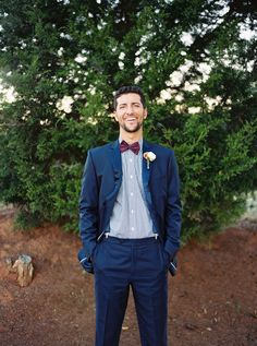 Groom in navy suit with blue patterened shirt and burgundy bow tie.