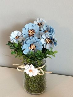 This simple glass jar houses a bouquet of hand painted pine cones in shades of blue. Arrangement is 8.25 inches tall.