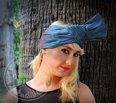 This outstanding turban hat, inspired on the 60's decade, is handmade in wild silk so its texture allows some perfect and espontaneous pleats that emphasise the changing colours, from a greyish blue with some hints of green to the wonderful red sheen. This marvelous turbant hat was specially created for a woman who feels elegant and who is brave enough to wear it, getting all the stared on her, without stoping being classy and restrained.