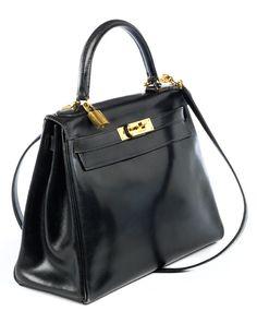 Ca. 22 x 28 x 10 cm. Schwarze Lederhandtasche mit goldfarbenen Beschlägen. Innenraum mit einem Reißverschluss- und zwei Steckfächern. Anbei Schultergurt,...