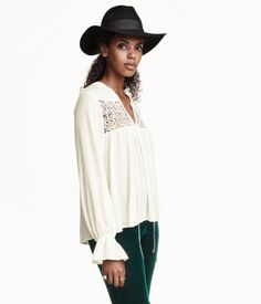 V-neck blouse in airy woven fabric. Ties at neck, lace inserts at front, and long sleeves with concealed elastication and ruffle at cuffs.
