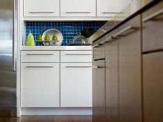 """Hardware can totally change the look of a kitchen,"" says Linda. Ceramic knobs, for example, would be too traditional, and half-moon bin pulls have that country feel. So she chose long brushed nickel pulls to give the flat-panel cabinets a modern look. ""I hung them horizontally just to mix things up."""