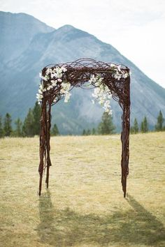 A tangle of vines (curly willow could give a similar effect) and a smattering of flowers give this wedding altar a beautiful rustic, yet modern look.