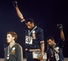 Tommie Smith (center) and John Carlos (right) make their controversial protest at the 1968 Olympics. Silver medallist Peter Norman, from Australia (left), empathised and wore an Olympic Project for Human Rights badge in support