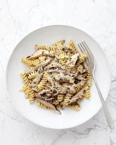 Creamy Shiitake Alfredo...Coarse salt and ground peppe**r 3/4 pound fusilli or other short twisted pasta** 2 tablespoons unsalted butter** 3 small shallots, thinly sliced** 3 garlic cloves, minced** 1 pound shiitake mushrooms, stemmed and thinly sliced or WHITE BuTTON Mushrooms** 2 tablespoons chopped fresh thyme leaves** 1/2 cup dry white wine, such as Sauvignon Blanc** 3/4 cup heavy cream** Grated Parmesan, for serving**