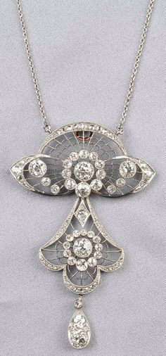 Edwardian Platinum and Diamond Pendant, the elaborate piercework form set with old European and rose-cut diamonds, approx. total wt. 3.00 cts., lg. 2 1/2 in., suspended from a delicate trace link chain.