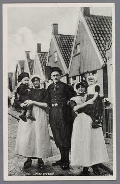 Twee vrouwen, een man en twee kinderen, allen in dracht, poserend in een straat in Wijk 3. 1930-1950 #Urk