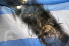 Argentina prosecutor killed       A woman holds up an Argentine flag smeared with black paint as people gather near the funeral home where a private wake is held for prosecutor Alberto Nisman in Buenos Aires, Argentina, Wednesday, Jan. 28, 2015.