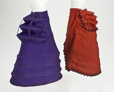 Date1872-1875 English: Woman's cage crinolettes (with bustles), English: Left: Purple cotton and wool twill with steel. Right: Red wool plain weave, cotton plain weave, cotton-braid-covered steel, cotton twill tape, and wool-braid trim Dimensions English: Right: Center back length: 35 in. (88.9 cm); Diameter: 25 in. (63.5 cm) ]Los Angeles County Museum of Art