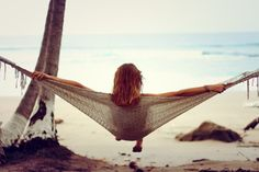 Hanging out in a Hammock, relaxing while looking out across the beach into the blue ocean