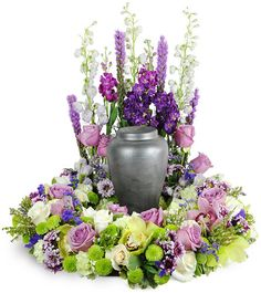 Made to surround an urn or framed photograph, this gorgeous, luxurious  wreath honors the memory of your loved one in a simply stunning manner.  Soothing green and lavender tones mix to create a calm and sophisticated  expression of compassion.This wreath features an array of orchids, roses, mums, delphinium, liatris, and more.