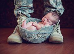Newborn baby in army helmet