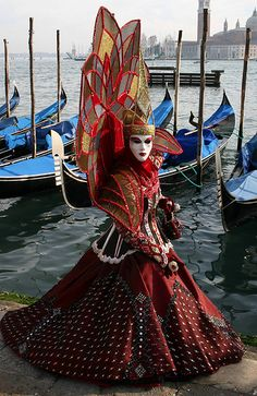 Carnevale in Venice, Italy...a beautifully costumed woman poses in front of gondolas.