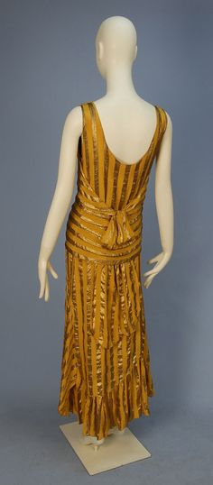 UNLABELED COUTURE SILK and LAME EVENING DRESS, 1920's. Sleeveless gold chiffon with wide gold lame stripe having over-bodice cut with deep V-back above two slits for self tie, flaring asymmetrical skirt having scalloped hem with ruffled insert and gore, chiffon under-dress. Hand sewn with couture details, probably French. Back