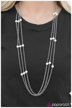White pearls dot three strands of silver chain that have been tiered to create the illusion of three separate necklaces. Features an adjustable clasp closure.  Sold as one individual necklace. Includes one pair of matching earrings.