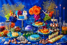 A wide range of colorful desserts based on the deep blue color and patterned after various sea creatures reminiscent of characters portrayed in the Little Mermaid fairy tale.