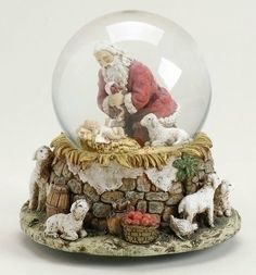 """5.5"""" The Kneeling Santa Claus with Baby Jesus Musical Christmas Water Globe by Roman. $59.99. From the Kneeling Santa Collection by Joseph's StudioItem #26782Santa looks lovingly upon Baby Jesus and is surrounded by adoring lambsPlays the tune """"O Come All Ye Faithful""""Dimensions: 5.5""""H x 5.25""""W x 5.25""""DMaterial(s): resin/stone mix/glass"""