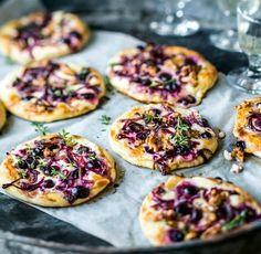 Knusprig-fluffiger Hefeteig gibt sich mit Schmand, roten Trauben und Zwiebeln, Walnüssen und Thymian die Ehre.