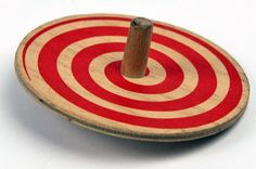 An old flat wooden spinning top with a red spiral painted around it and a small dowel in the middle
