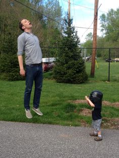 Photo of a Little Kid in a Darth Vader Helmet 'Vadering' a Grown Man