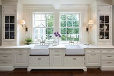 Sconce lighting and double farmhouse sinks with bridge faucets - gorgeous!