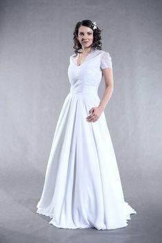Svatební+šaty+s+kolovou+sukní+Šaty+s+krajkovým+živůtkem+a+kolovou+sukní+z+jemného+žoržetu,+malé+krajkové+rukávky,+vzadu+skrytý+zip.+Špičatý+výstřih+je+vhodný+pro+větší+prsa.+Velikost+40,+je+možné+na+objednávku+ušít+jinou.