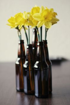beer bottle vases. so tacky but a cute idea for the bathroom maybe? lol