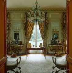 Duke & Duchess of Windsor's Paris home ~ The antique table in front of the window in the salon was used by the Duke of Windsor when he signed the Instrument of Abdication curule ottomans, colored glass chandelier, print curtains, gilt consoles.