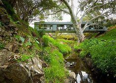 Conheça a casa que tem formato de ponte e possui integração a um riacho na Austrália.