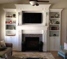Stone fireplace, mounted tv, side storage and bookshelves. But too much white?