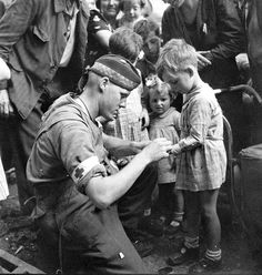 Private GR MacDonald of The Toronto Scottish Regiment photographed giving first aid to an injured French boy in Brionne, 25 August 1944