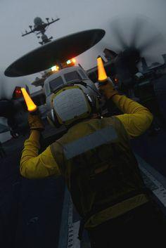 A Sailor directs an E-2C aboard USS John C. Stennis. by Official U.S. Navy Imagery