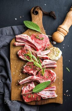 Raw uncooked lamb chops with herbs and spices on rustic wooden board over dark  background by Anna Ivanova on 500px