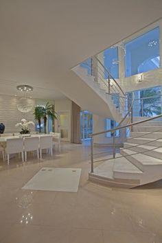 Neste ambiente, assinado pelo arquiteto Nícolas Aquiles Kílaris, a escada é feita de mármore Carrara. O formato faz parte do estilo do profissional, que valoriza as formas orgânicas.