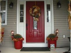 Deep red front door with tan siding